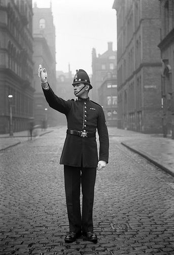 A wonderfully preserved image of a Manchester City Police officer on point duty in central in the city around 1914.    Before the electronic traffic light became widespread, officers would control junctions during busy periods. This practice was known as point duty and each officer would be allocated a 'point' and set times at which he was to attend. http://www.gmpmuseum.com