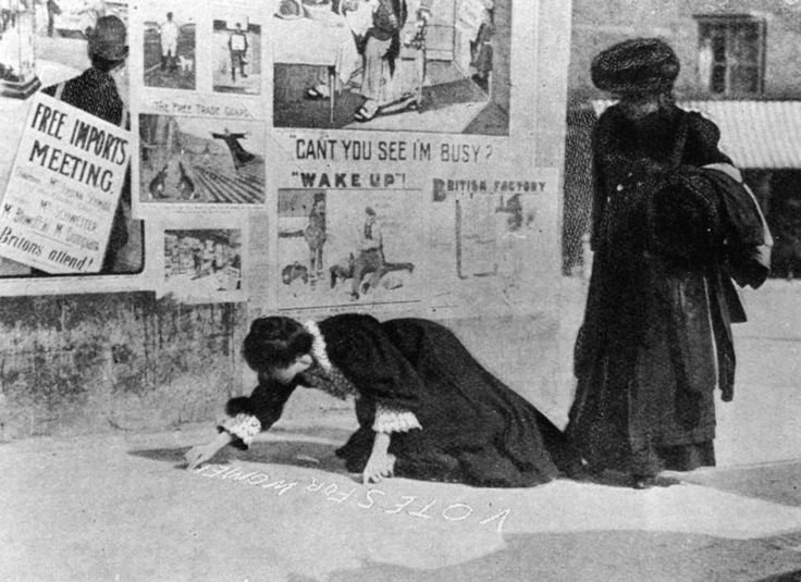 Suffragettes Annie Kenney and Mary Gawthorne painting a pavement with a slogan…