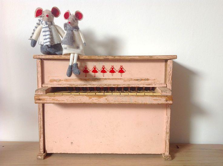 Kinderpiano, jaren 60  Oude poederroze kinderpiano, gedecoreerd met rode ballerina's. De verf heeft sleetse plekken maar dat is juist de charme van dit leuke kinderspeelgoed.