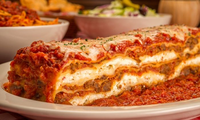 Traditional Italian food served family style including pizza, pasta, and more