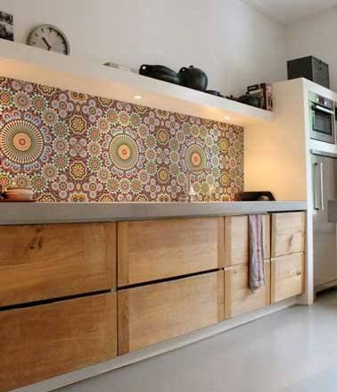 Cette crédence de cuisine en carrelage à motifs bege et jaune et marron impose son style éthnique dans la cuisine. Une harmonie déco avec avec le plan de travail en pierre et les meubles bois
