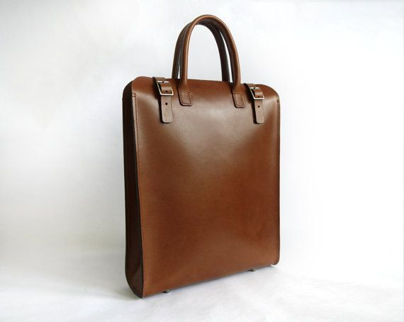 "This sleek leather tote couples a minimal aesthetic with a hint of vintage charm, the perfect accessory for a female or male wearer. Crafted from hand dyed vegetable tanned leather, the finish is supple yet durable, perfect for everyday wear. Featuring one main compartments, and a removable leather clutch, it's the perfect size for a 13"" laptop, with more than enough room to spare. From professional to casual, it's a great bag for anyone who loves high quality materials and minimal styling…"