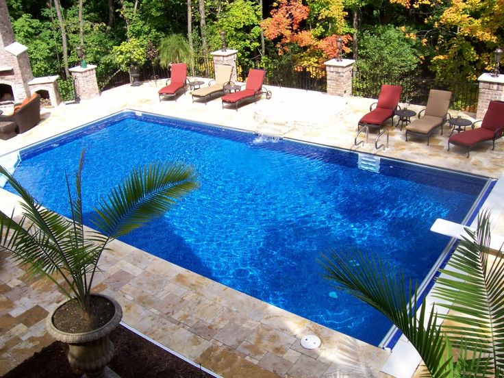 swiming pools awesome rectangle pool design with red pool lounge chairs also backyard plants and marble - Inground Pool Design Ideas