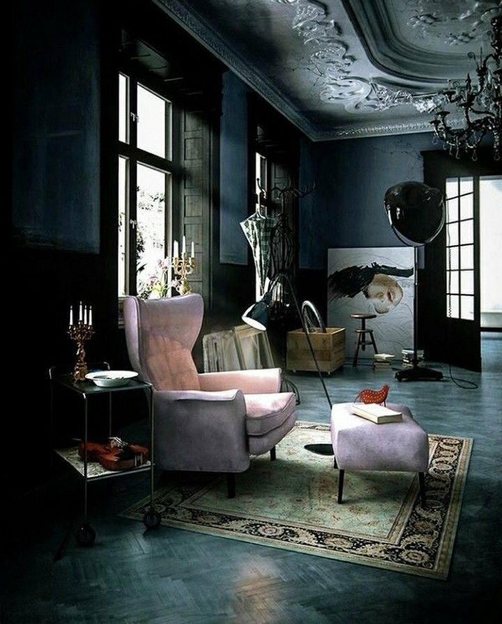 a dark and moody living room with a little pink chair