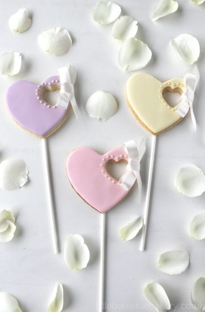 Heart cookie favours  -  Our bride requested favours to match her pretty pastel Wedding colours.   Elegant with the satin tied bow detail and adding the royal iced cookie on a wand injected a bit of fun too.  Every cookie for each Wedding guest was individually bagged with a personalized name tag.  Little Boutique Bakery