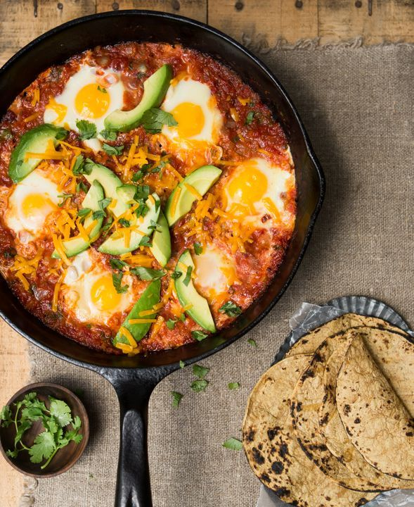 Go non-traditional for Christmas brunch: crazy good Huevos Rancheros. Eggs cook gently in a chipotle-spiced, bacon-flecked sauce topped with cilantro and Cheddar. All made in one pan!.