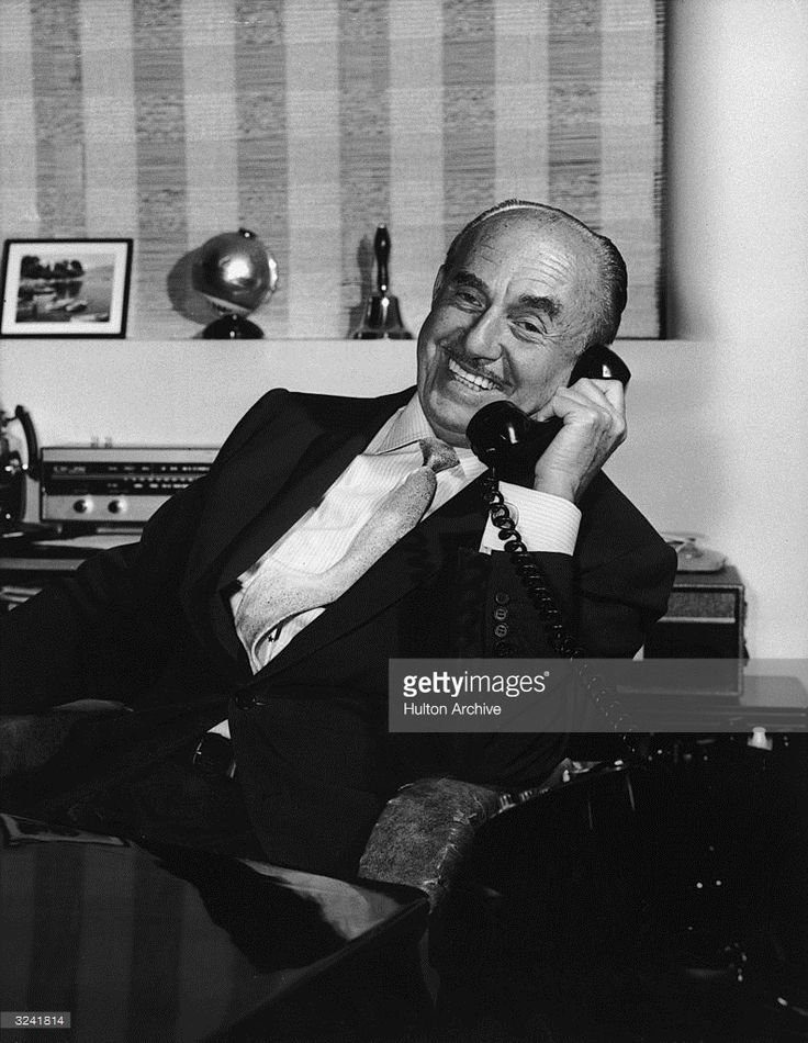 Canadian-born film producer Jack L Warner (1892 - 1978), of Warner Brothers Pictures, smiles while talking on a telephone, 1950s.