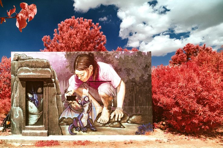 Graffiti on the wall of a cabin, depicting a girl petting a small dragon. A photograph I took in the style of the old Kodak EIR colour infrared slide film.