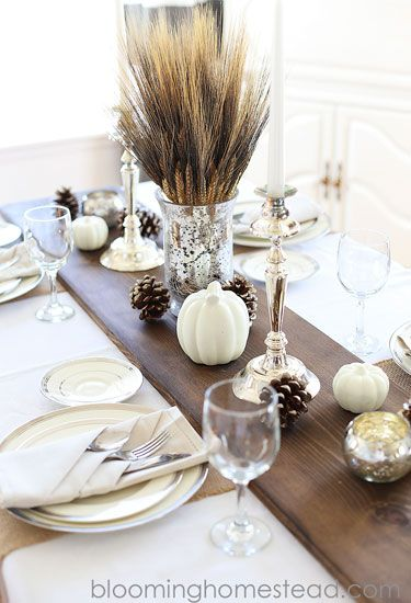 Metallic candle holders, frosted pinecones, and white pumpkins stand out against a dark stained wood table runner.: