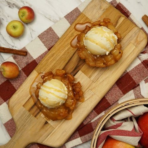 Recipe with video instructions: Inspired by the blooming onion, this spiced apple treat is packed with sweet, crispy goodness. Ingredients: 2 apples, 2 cups beignet or fritter mix, 1 1/2 cups water, 2 teaspoons pumpkin pie spice, 2 tablespoons brown sugar, Oil for frying, Ice cream and caramel sauce for a la mode