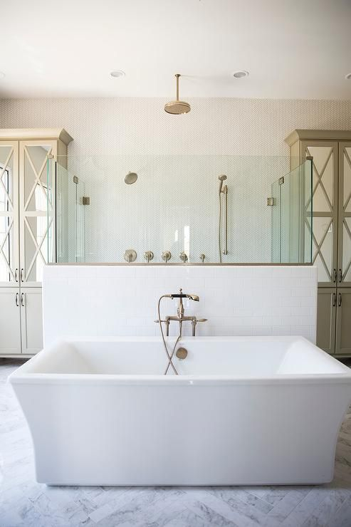 Beautifully appointed bathroom boasts a rectangular freestanding tub placed on marble herringbone floor tiles in front of a white subway tile and glass walk in shower enclosure.