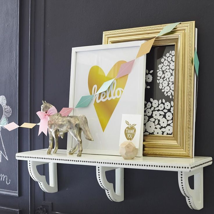 Design Tip: Don't be afraid to put a framed print in front of an existing one! For an additional pop of color add some fun garland across your Transitional Nailhead Shelving! Try making the one featured in #revveduprooms 😃 #TransitionalDecor