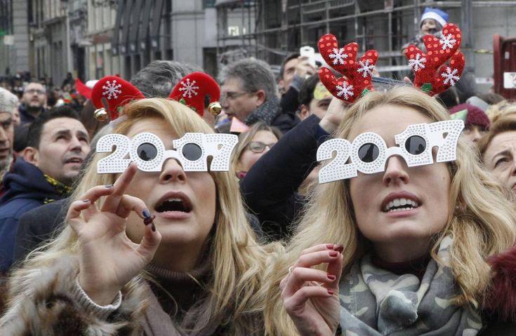 Muitas pessoas caminham esta manhã pela Puerta del Sol em Madri, comendo uvas ao meio-dia, como prelúdio para a meia-noite.