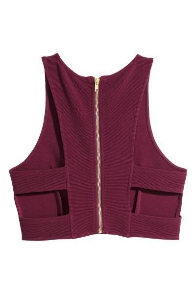 Top corto: Top corto en punto de canalé. Modelo sin mangas con secciones laterales abiertas y cremallera visible en la espalda.