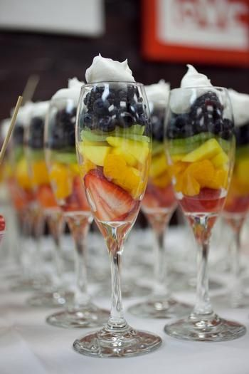 Simple but effective, pretty, and party-perfect: find plastic wine glasses in the wedding section of the dollar store and layer fruit inside.  So much more elegant than making up one big fruit salad.