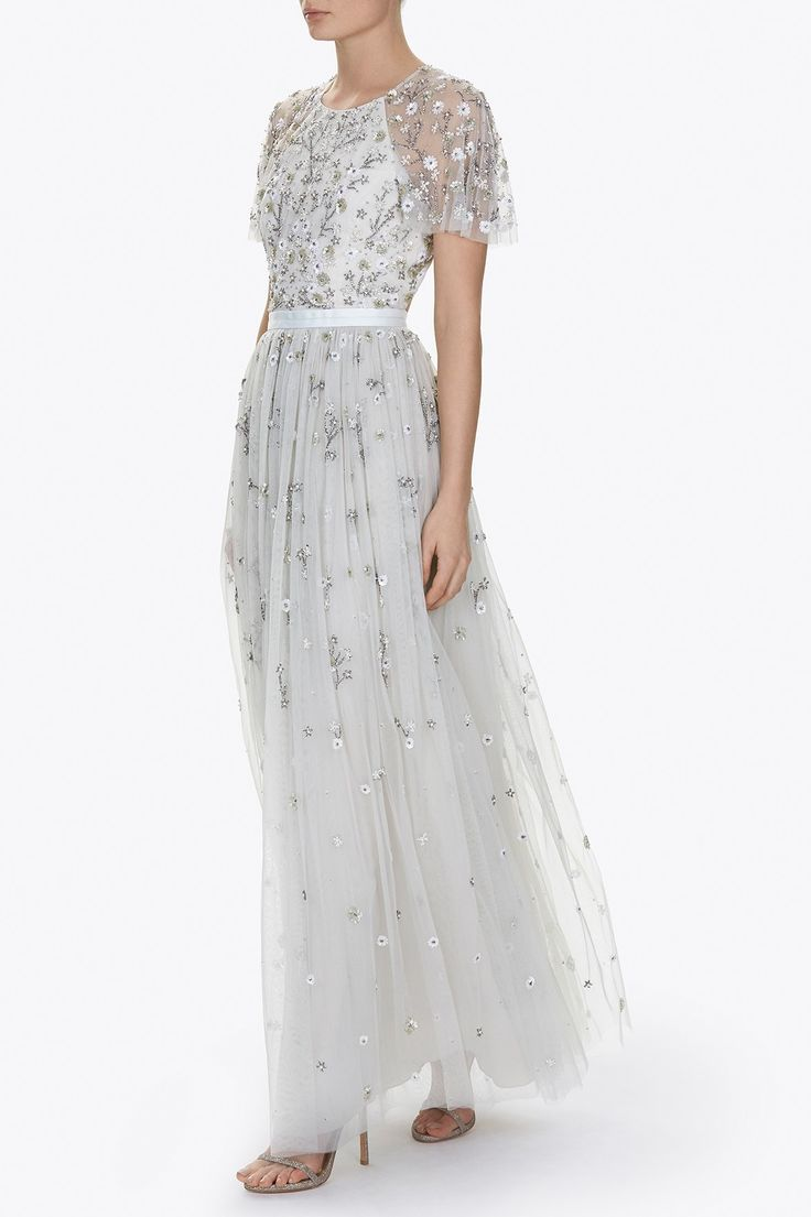 The Starlit Gown is decorated with a delicate, scattering embellishment, which was inspired by Victorian Floral Lace. The florals are depicted in iridescent, silver and gold components which add a beautifully subtle, all-over shimmer. The soft spearmint base compliments the pretty embellishment. The backless detail adds a feminine edge to this elegant tulle shape.