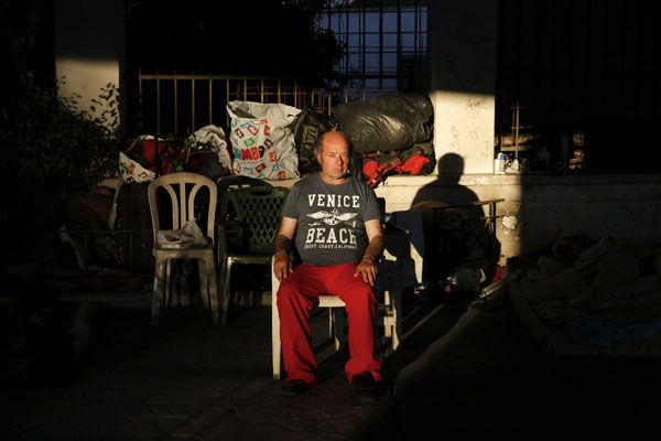 Giorgos,50, sits by his belongings  under a bridge where he lives with a group of  other homeless Greeks in central Athens.   REUTERS/Yannis Behrakis