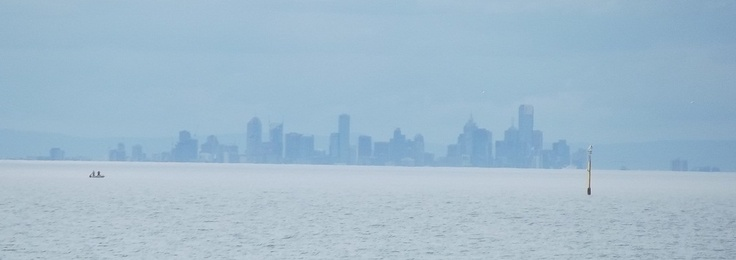 Melbourne from across the bay. Do you envy the two people in the boat?