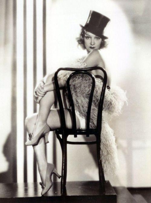 Florence Desmond. top hat. boa. cabaret chair. beautiful lighting