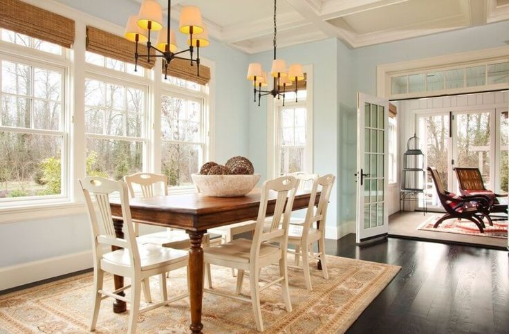 This coastal contemporary dining room features rich dark hardwood floors and breezy French doors that lead into a sunroom. Natural fiber shades keep the windows feeling open and bright, without sacrificing any privacy.