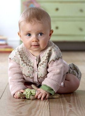 Den søde trøje er strikket i pastelfarver, der klæder en lille pige