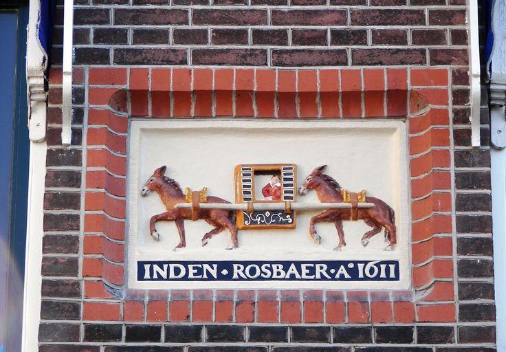 """In den rosbaer, gevelsteen op de Botermarkt in Haarlem. Een rosbaer is een soort 17e eeuwse taxi, in dit geval zijn de dieren muilezels. Muilezels zijn paardachtigen, vandaar de benaming """"ros""""."""