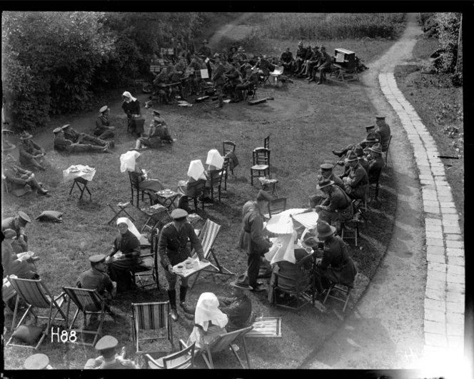 General view of the garden party held by the World War I nurses at the New Zealand Stationary Hospital, probably at Hazebrouck, France. Guests sit on chairs or lie on the grass. Matron Frances Price sits, bottom left, talking to General Russell. In the background an army orchestra has stopped playing. Photograph taken 24 June 1917 by Henry Armytage Sanders