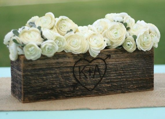 Love this for some of the centerpieces. Barn Wood Rustic Vase Centerpiece Personalized (item E10165). $24.99, via Etsy.