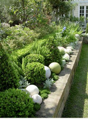 Boxwood balls and stone balls on top of the garden wall. thompson and hanson Image Via:  cleverconfidante.blogspot.com