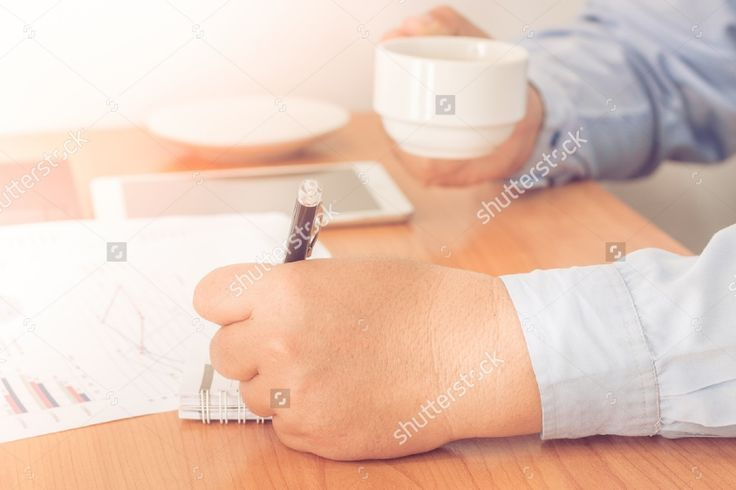Businessman working on office desk. Writing something on notebook.Holding a coffee cup in a hand. Blurred background, Vintage concept. #business #businessman #office #background #notebook