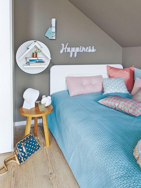 Wie in einer Höhle schmiegt sich das Bett in die Ecke unter der Dachschräge, links wird es obendrein vom Kleiderschrank abgeschirmt – sehr gemütlich! Wand und Decke in Anthrazit verstärken diesen Eindruck noch.