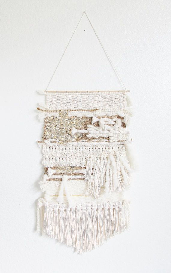 This stylish wall hanging was made by hand using off white yarns, brown burlap yarns and has a lot of texture. It has a beautiful calming and natural look. The bottom fringe has a soft v-shape in cotton yarn. Gold leaf add texture at the top of the weaving and make it unique. It hangs from a 12 wide wooden rod and is ready to hang. Due to the handmade process of this art form two weaves will never be exactly the same.     The weaving itself measures 11 by 24 for a total of 34 long from where…