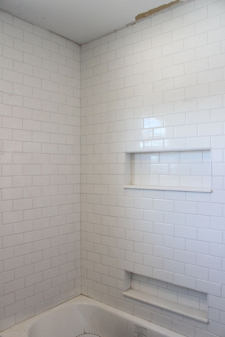 White subway tile shower, Frost grout by Mapei.  Like the idea to go all the way to the ceiling and the cut-out for the toiletries