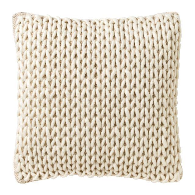 Cojín de lana y algodón con un ligero y discreto acabado trenzado. Tiene cierre de cremallera y el relleno es defibra hueca siliconada.