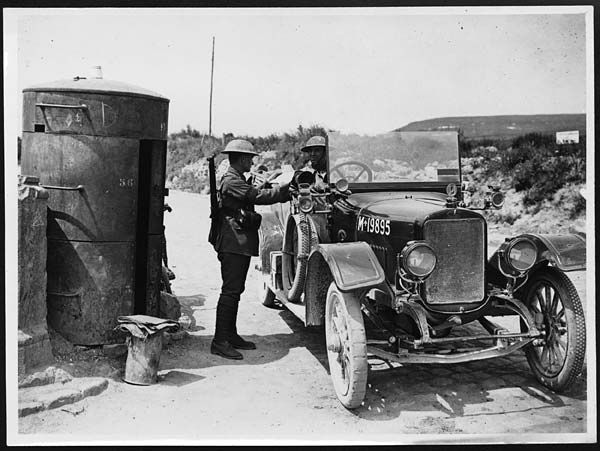 WW1. Examining post in the forward area.  This photograph shows a sentry who is examining the papers of another soldier in an army car. The moveable pillbox behind the sentry is basically a metal cylinder. It would have given some protection from shelling, but must have been both hot and claustrophobic. -controversialdocumentaries blogspot