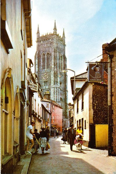High Street, Cromer, Norfolk, 1960s. (Old colour photo of Hight Street, Cromer, Norfolk, England, UK in the 1960s.) with the medieval  St Peter and St Paul's Church in the background