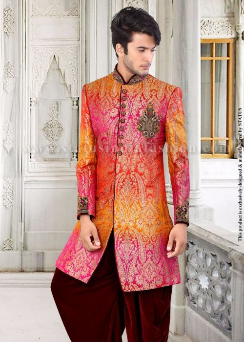 <p>This classic indo western sherwani with the blend of ochre, pink and orange colors is made out of brocade and silk fabric with a printed design overall. The designer mandarin collar, matching buttons and a beautiful patch on the left chest and the cuffs is eye catchy. Complimentary to the kurta is the maroon velvet dhoti, making it a complete indo western outfit.</p> <p>Mojari shown in the image is only for photography purpose.</p> <p>To choose a de...