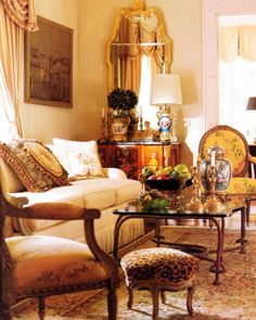 Country French living room - gilded mirror, fauteuil side chairs, inlay chest, leopard footstool and aubusson pillows.