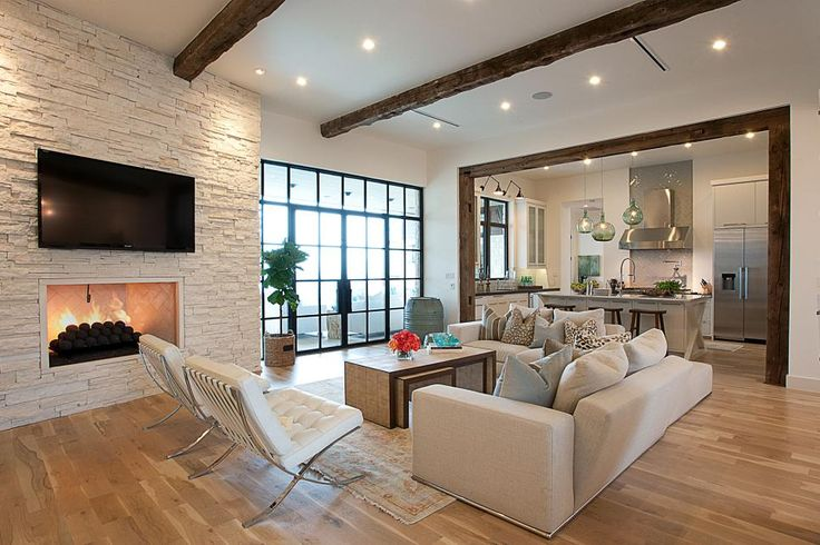 Rough-hewn ceiling beams and a stacked stone fireplace surround add texture and interest to flat white walls. White Barcelona accent chairs introduce a sleek, midcentury modern touch.