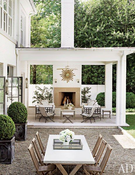 Suzanne Kasler's terrace.  Love how the limestone portico over her front door is carried over to the fireplace here.
