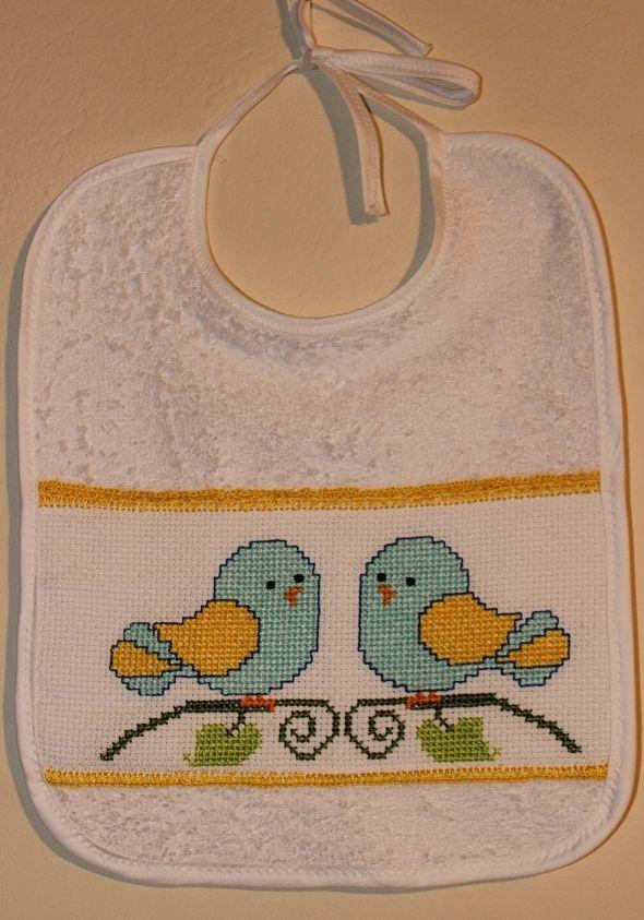 Bavaglino in spugna di cotone ricamato a punto croce. Il disegno ritrae due uccellini molto colorati. Il bavaglino è di colore bianco ed ha un inserto di tela aida, profilato all'uncinetto con cotone giallo. Il bavaglino ha forma rettangolare e misura 28x22cm.
