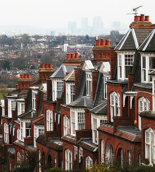 The Edwardian houses of steep Muswell Hill, a suburban street in the northern part of greater London, England. The background view is Canary Wharf; one of London's major business districts.