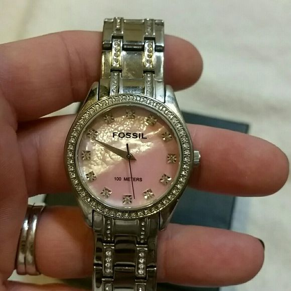 Authentic Fossil watch. PRICE REDUCED!! Beautiful, authentic Fossil watch with pink mother of pearl face, with crystal accents on watch face as well as on band. Worn but not often and is in excellent condition. It does not have the box (but I can check). I had links taken out since my wrists are small. I may still have the extra links to put back to make bigger, also will need a new battery.  Selling because I have one exactly like this but with white face that I wear more. Fossil…