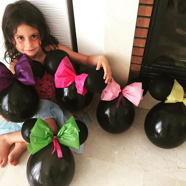 Minnie Mouse party decoration idea.  Easy cheap and very effective - 3 black balloons, some glue dots and a bit of tissue paper- we hung them from trees.