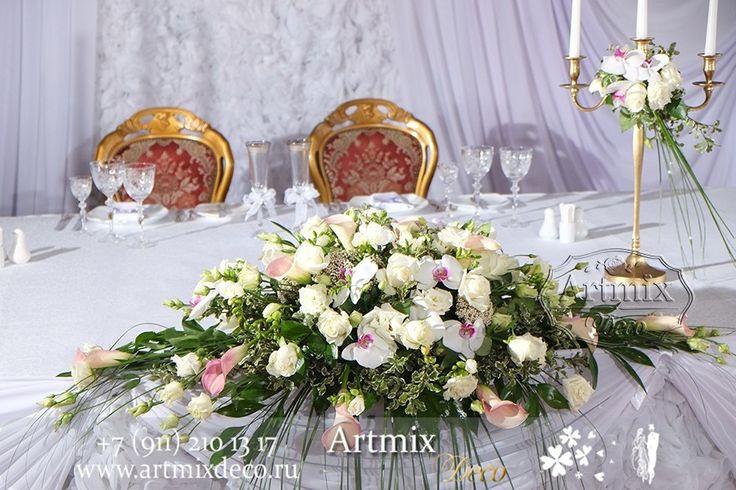 Цветы на свадебном столе молодожен. Живыми цветами на банкете принято украшать стол жениха и невесты.  Нежные орхидеи и каллы на центральной композиции стола.