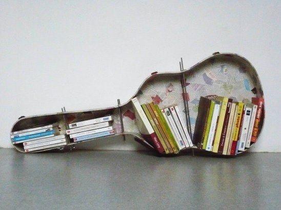 DIY boekenplank. Benodigdheden: gitaarkoffer, dik ijzerdraad, papier om de binnenkant mee te beplakken, spuitlijm, boormachine. Boor gaatjes in de koffer om de dikke ijzerdraad doorheen te steken als steun voor de boeken. Beplak eventueel de binnenkant van de gitaarkoffer met papier.