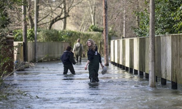 Residents of Henley-on-Thames walk along a flooded street