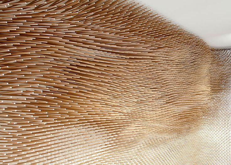 22,000 wooden sticks form a textured wall inside this boutique in Stuttgart.