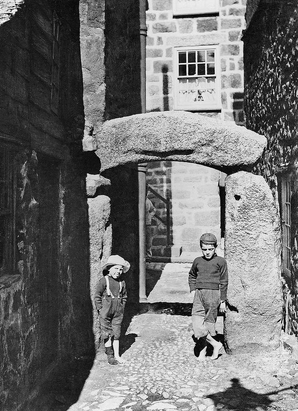 St. Ives, Cornwall - A view of the well known granite arch that leads into Hick's Court from the Digey. The lad on the right looks particularly morose - possibly bored from waiting for the photograper to set up his camera! The photographer has chosen the time of day very carefully, when the sun is illuminating the archway and the narrow entrance.
