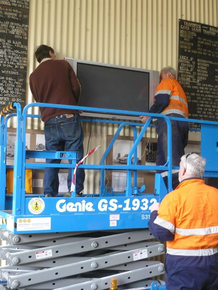 Three blokes - scissors lift - large heavy tv - fitting it onto a bracket they can't see. What could possibly go wrong?